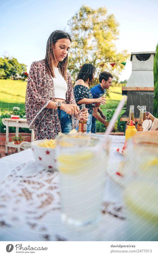 Frau öffnet Bierflasche am Sommergrill Essen Mittagessen Getränk Limonade Alkohol Flasche Trinkhalm Lifestyle Freude Glück Freizeit & Hobby Garten Tisch