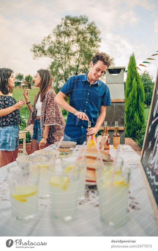 Mann öffnet Bierflasche am Sommergrill Essen Mittagessen Limonade Alkohol Flasche Trinkhalm Lifestyle Freude Glück Freizeit & Hobby Garten Tisch sprechen Frau