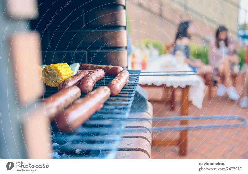 Würstchen und Maiskolben im Grill gekocht Wurstwaren Gemüse Mittagessen Lifestyle Freude Glück Erholung Freizeit & Hobby Sommer Garten Tisch sprechen Frau