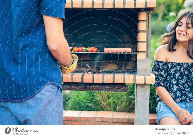 Mann kocht Würstchen und Gemüsespieße im Barbecue. Wurstwaren Lifestyle Freude Glück Erholung Sommer Garten sprechen Frau Erwachsene Freundschaft Hand Natur
