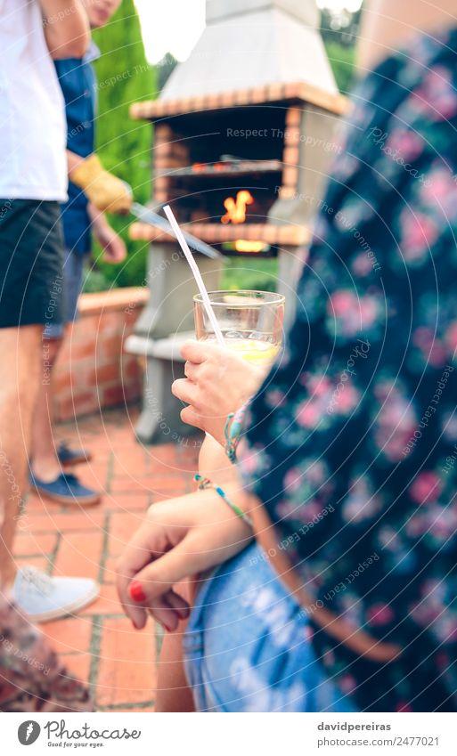 Frau mit Limonadenglas und Freunden beim Kochen im Grill Wurstwaren Mittagessen Lifestyle Freude Glück Erholung Freizeit & Hobby Sommer Garten sprechen
