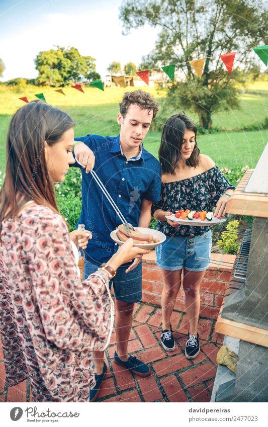 Gruppe von Freunden, die bei einem Sommergrill kochen. Gemüse Mittagessen Alkohol Bier Teller Flasche Lifestyle Freude Glück Freizeit & Hobby Garten sprechen