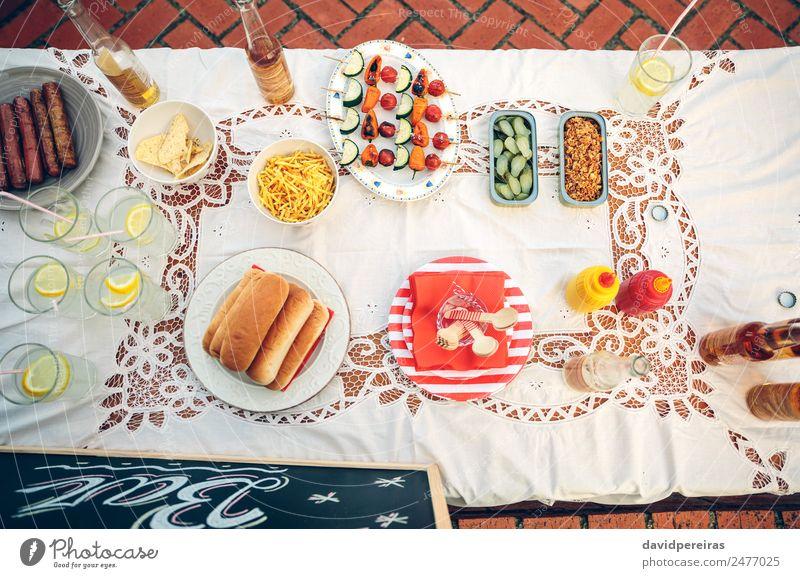 Tisch mit Speisen und Getränken im Sommerfest Gemüse Brot Brötchen Mittagessen Fastfood Limonade Bier Teller Flasche Glück genießen frisch lecker gelb trinken
