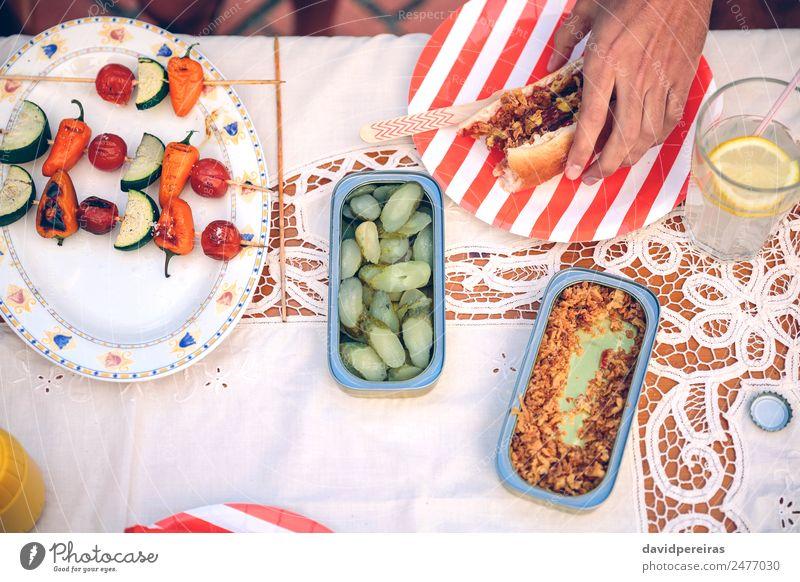 Männliche Hand hält Hot Dog auf rot gestreifter Platte Wurstwaren Brot Brötchen Mittagessen Fastfood Limonade Teller Lifestyle Freude Glück Sommer Mensch Mann