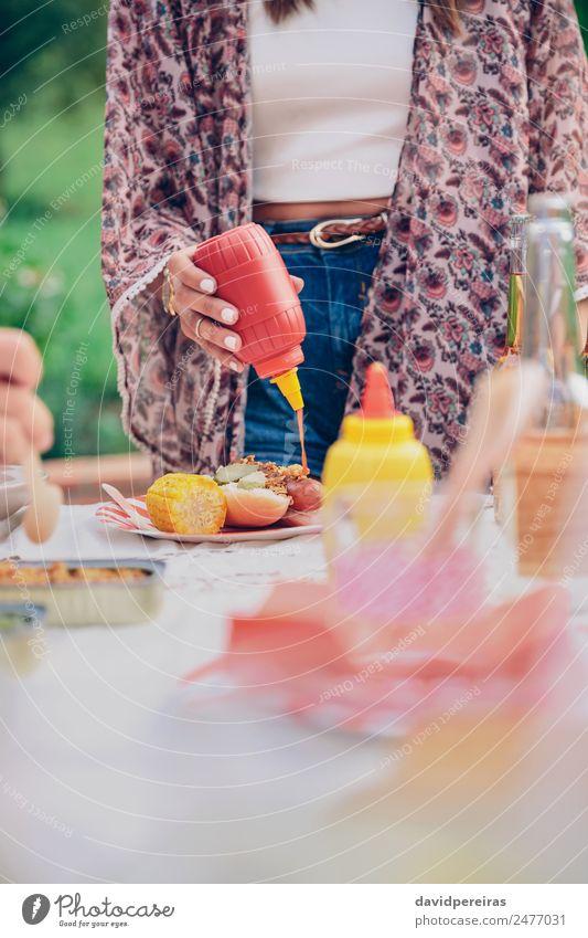 Frau Hand gießt Ketchup über einen amerikanischen Hot Dog. Fleisch Wurstwaren Brot Brötchen Mittagessen Fastfood Bier Teller Flasche Lifestyle Freude Glück