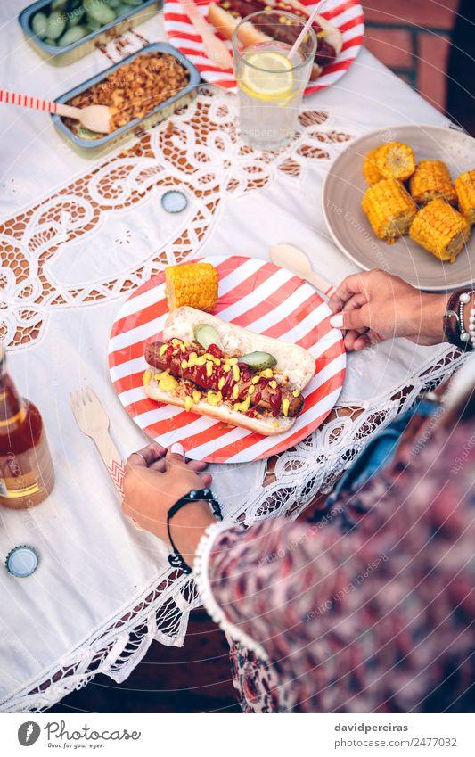 Frauenhalteplatte mit Hot Dog und Mais Wurstwaren Brot Brötchen Fastfood Limonade Alkohol Bier Teller Flasche Löffel Lifestyle Freude Glück Sommer Tisch