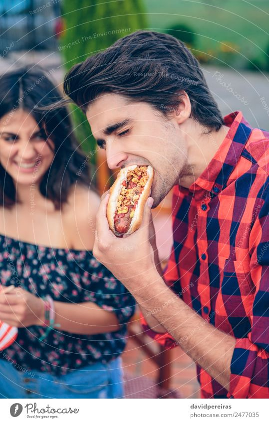 Junger Mann isst Hot Dog und Frau lacht im Hintergrund. Wurstwaren Brot Brötchen Mittagessen Fastfood Lifestyle Freude Glück Sommer Erwachsene Freundschaft Hand