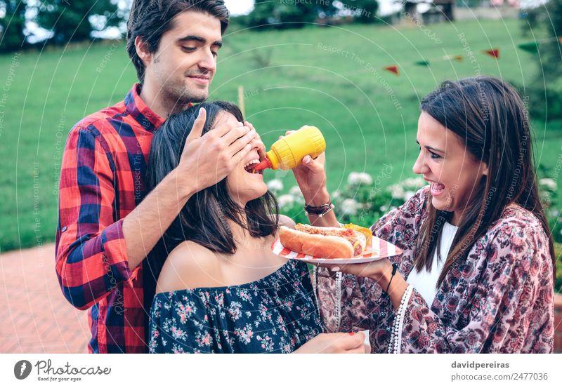 Mann hält Hot Dog im Barbecue mit Freunden. Wurstwaren Essen Fastfood Teller Lifestyle Freude Glück Sommer Frau Erwachsene Freundschaft Mund Hand genießen
