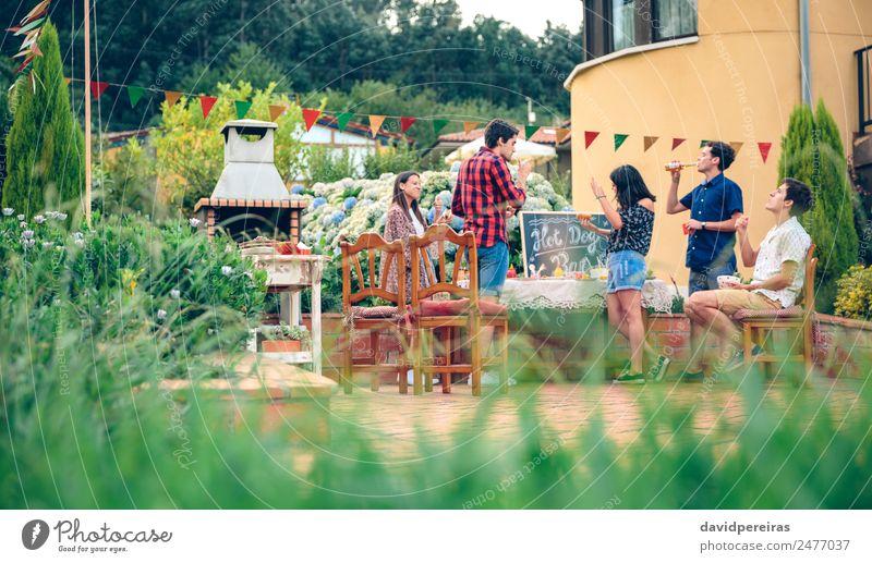 Gruppe von Freunden, die bei einem Sommergrill genießen. Fleisch Wurstwaren Mittagessen Alkohol Bier Flasche Lifestyle Freude Glück Freizeit & Hobby Garten