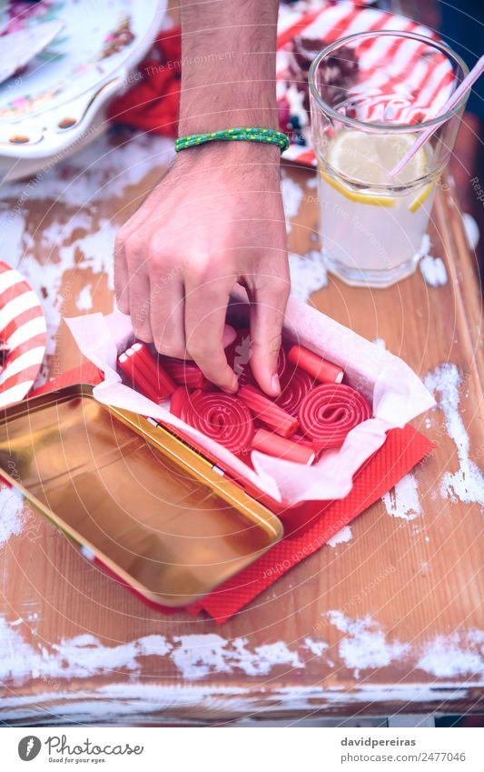 Männliche Handpflückung Süßigkeiten aus der Schachtel in einem Sommerfest Dessert Mittagessen Limonade Teller Lifestyle Freude Glück Freizeit & Hobby
