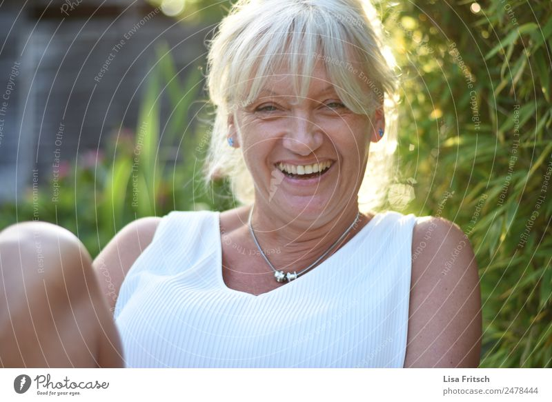 Lachende Frau im Grünen. schön Gesundheit Ferien & Urlaub & Reisen feminin Erwachsene 1 Mensch 45-60 Jahre Natur Sträucher Halskette blond weißhaarig Pony
