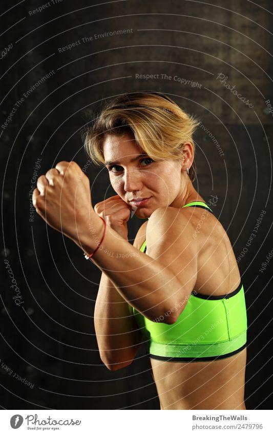 Nahaufnahme Frontalporträt einer jungen sportlichen Frau in Sportkleidung in einer Turnhalle vor dunklem Hintergrund, stehend in Boxhaltung mit Händen und Fäusten, Blick in die Kamera