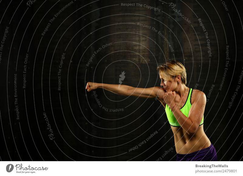 Close up Seitenansicht Profil Porträt einer jungen sportlichen Frau Schattenboxen in Sportkleidung in der Turnhalle über dunklen Hintergrund, wegschauen