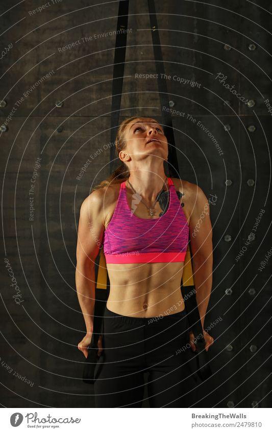 Eine junge, sportliche Frau mittleren Alters beim Crossfit-Training, die mit Trx-Suspension-Fitnessbändern vor dunklem Hintergrund trainiert, Vorderansicht, Blick nach oben