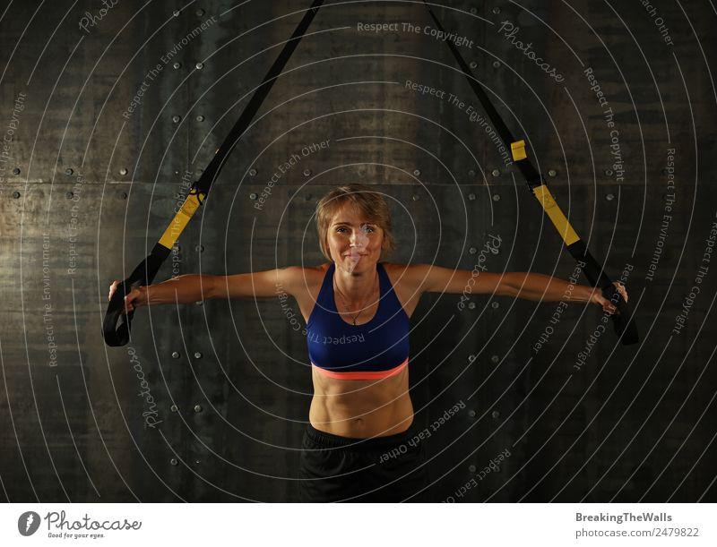 Eine junge, sportliche Frau mittleren Alters beim Crossfit-Training, die mit Trx-Suspension-Fitnessbändern vor dunklem Hintergrund trainiert, Vorderansicht, Blick in die Kamera