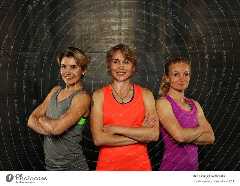 Nahaufnahme von vorne Porträt von drei jungen und mittleren Alter sportliche Frauen in Sportkleidung in der Turnhalle über dunklen Hintergrund, Blick auf die Kamera