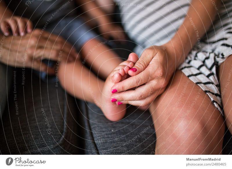 Nahaufnahme einer Mutter, die den Fuß eines Kindes hält. Massage Baby Frau Erwachsene Eltern Vater Familie & Verwandtschaft Kindheit Hand Finger 3 Mensch