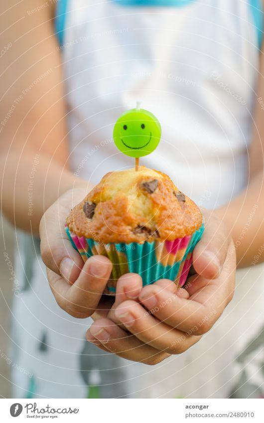 Cupcake und Kerze lächelnd in den Händen eines Kindes. Lebensmittel Dessert Glück Tisch Geburtstag Gastronomie Junge Hand 1 Mensch Papier Lächeln lecker grün