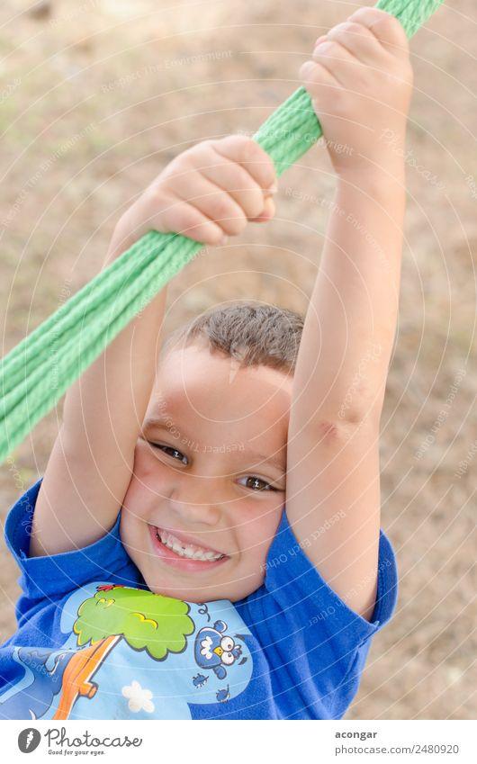 Der Junge hat Spaß, hält sich an einem Seil fest. Freude Glück schön Gesicht Klettern Bergsteigen Kind Mensch 1 3-8 Jahre Kindheit genießen lustig Fröhlichkeit
