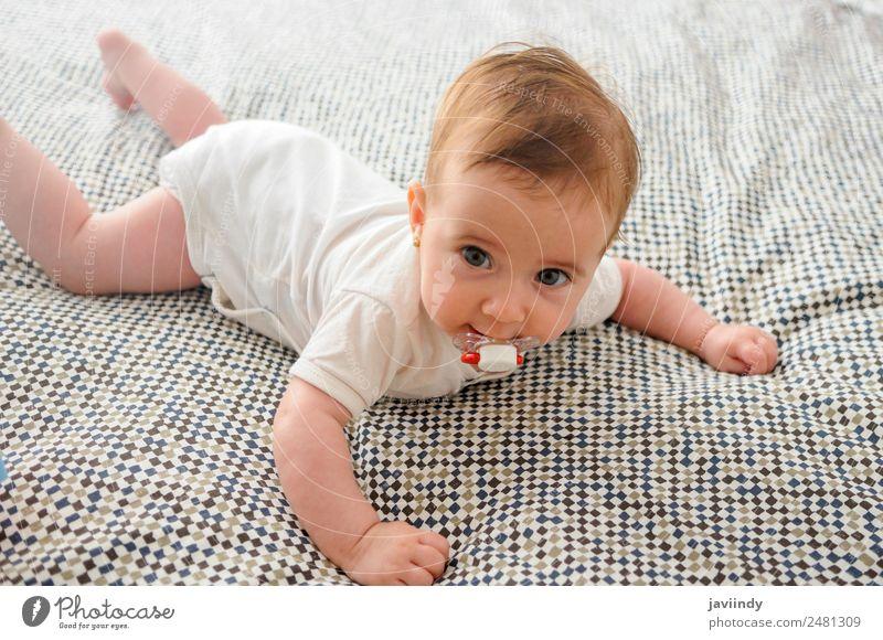 Glückliches Mädchen im Alter von vier Monaten, auf dem Bett mit Schnuller. schön Gesicht Leben Kind Mensch Baby Kindheit 1 0-12 Monate Lächeln schlafen klein