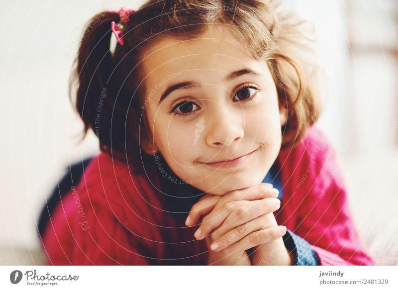 Liebenswertes kleines Mädchen mit süßem Lächeln, das auf dem Bett liegt. Freude Glück schön Gesicht Kind Mensch Kindheit 1 3-8 Jahre niedlich weiß heiter jung