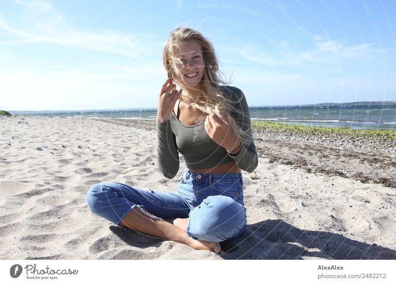 Blonde, junge Frau am Ostseestrand mit wehendem Haar Lifestyle Freude Glück schön Wohlgefühl Sommer Sommerurlaub Sonne Sonnenbad Strand Meer Junge Frau