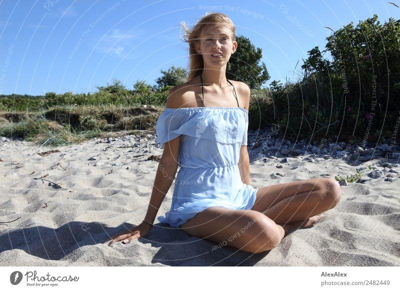 Junge Frau sitzt im Schneidersitz in einem kurzen Sommerkleid am Strand Lifestyle schön Leben Sommerurlaub Sonne Sonnenbad Jugendliche 18-30 Jahre Erwachsene