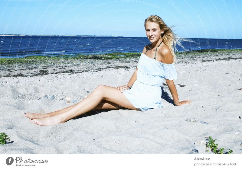 Junge, schlanke, langebeinige Frau am Ostseestrand in einem Sommerkleid Lifestyle schön Leben Wohlgefühl Sommerurlaub Sonne Sonnenbad Strand Meer Junge Frau