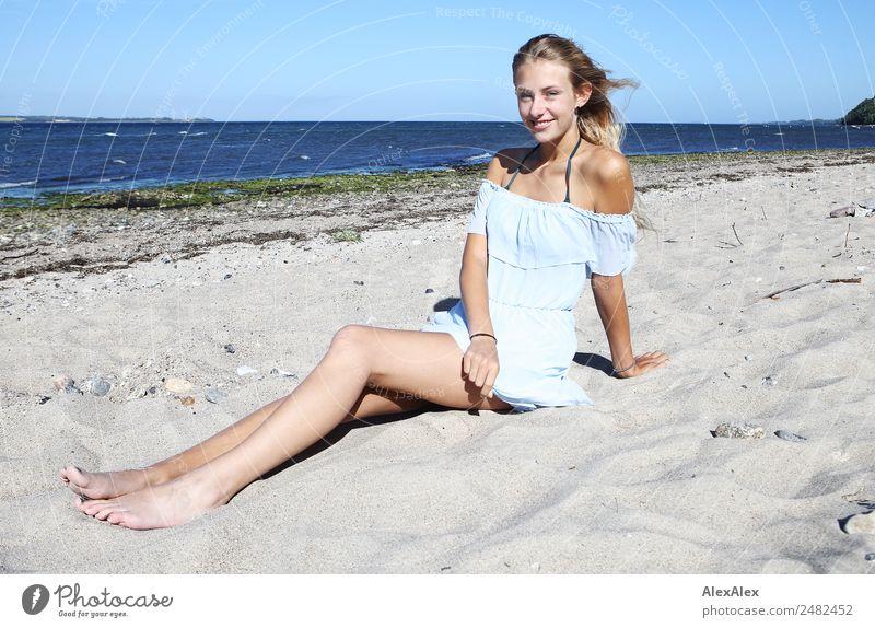 Junge, langbeinige Frau sitzt am Ostseestrand Lifestyle Freude Glück schön Wohlgefühl Erholung Sommer Sommerurlaub Sonne Sonnenbad Strand Meer Junge Frau