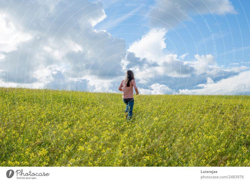 Mädchen, das auf einem Feld mit gelben Blumen spazieren geht, sonniger Tag Freude Gesundheitswesen Wellness Sinnesorgane Erholung Duft Ferien & Urlaub & Reisen