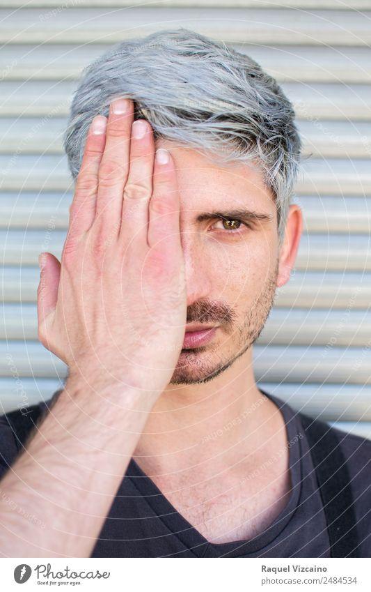 Porträt eines Mannes, der ein Auge mit der Hand bedeckt. Lifestyle Haare & Frisuren Gesicht Mensch maskulin Junger Mann Jugendliche 1 18-30 Jahre Erwachsene
