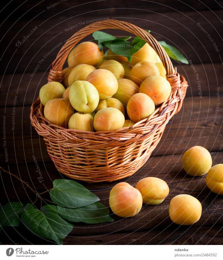 Reife gelbe Aprikosen Frucht Ernährung Vegetarische Ernährung Diät Tisch Natur Blatt Holz frisch natürlich saftig braun Farbe Korb Ackerbau Hintergrund