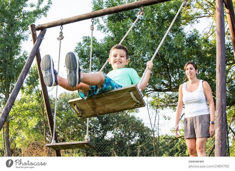 Mutter schwingt ihren Sohn auf einer Schaukel. Lifestyle Freude Glück schön Erholung Freizeit & Hobby Spielen Kind Mensch Junge Frau Erwachsene Mann Eltern