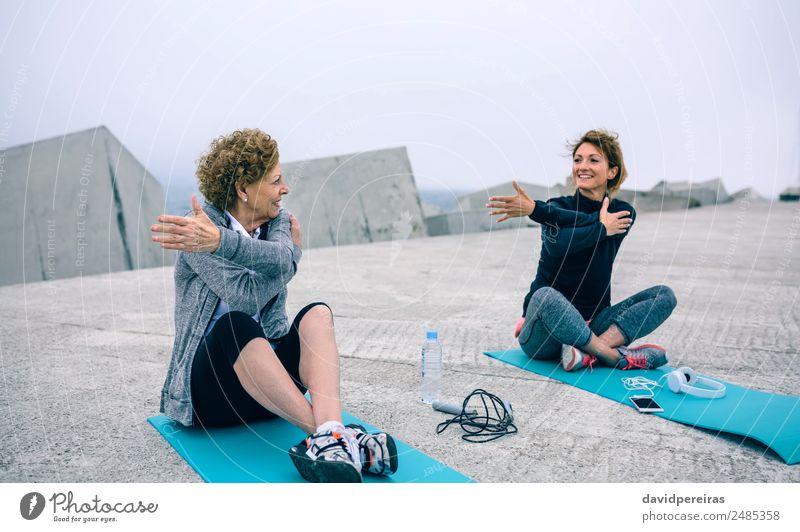 Ältere Frau beim Stretching mit weiblichem Coach Flasche Lifestyle Wellness Freizeit & Hobby Sport Schule PDA Mensch Erwachsene Mutter Großmutter Arme Nebel