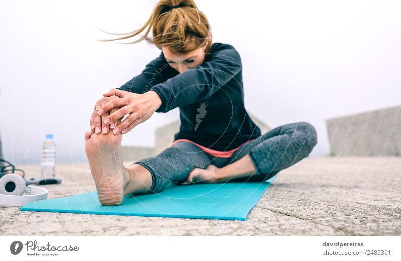 Junge Frau, die ihre Beine am Pier ausstreckt. Flasche Lifestyle schön Wellness ruhig Winter Sport Yoga Mensch Erwachsene Hand Fuß Nebel Beton Fitness