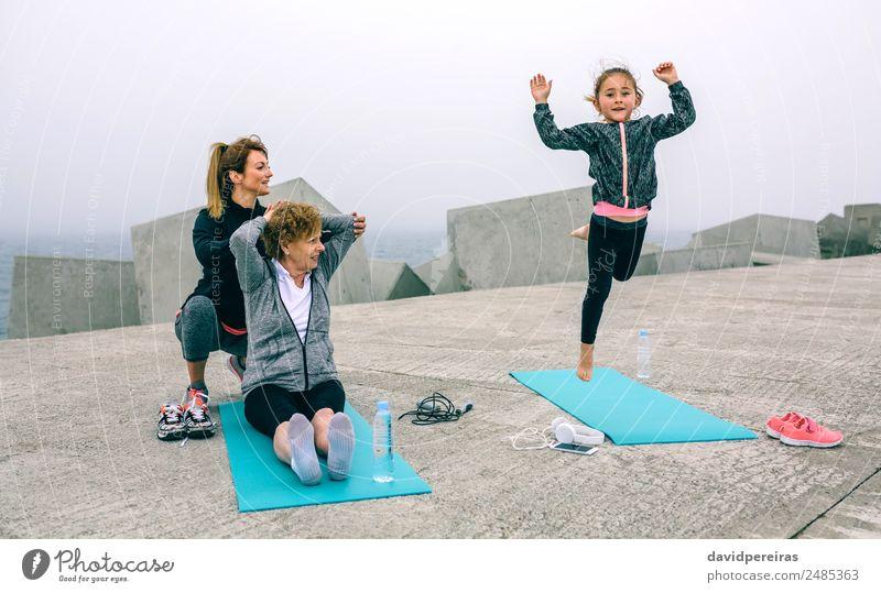 Mädchen springen, während Frauen trainieren. Flasche Lifestyle Glück Wellness Sport Kind Telefon Mensch Erwachsene Mutter Großmutter Familie & Verwandtschaft