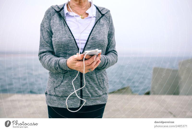 Senior-Sportlerin hält ihr Smartphone in der Hand. Lifestyle Freizeit & Hobby Meer Dekoration & Verzierung Musik Telefon PDA Technik & Technologie Mensch Frau