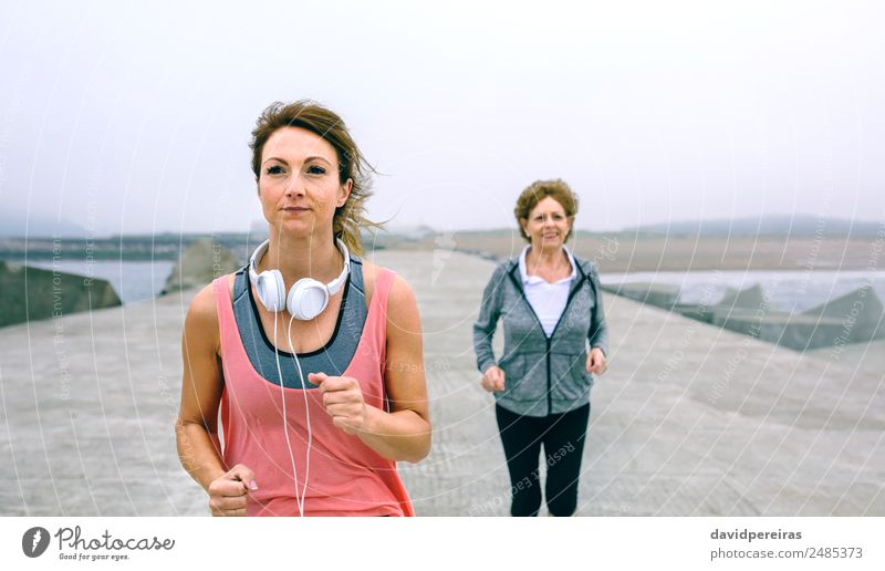 Junge und ältere Sportlerinnen laufen am Seepier Lifestyle Wellness Meer Joggen Mensch Frau Erwachsene Mutter Großmutter Nebel Beton alt Fitness Lächeln