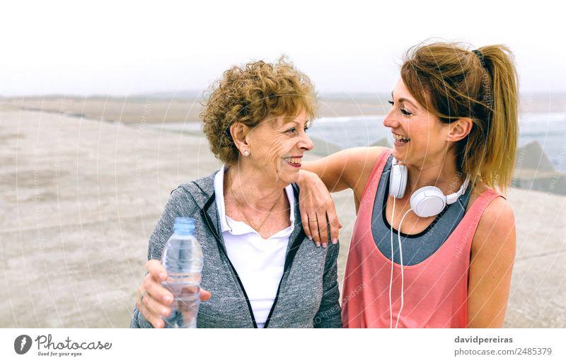 Seniorensportlerin lacht mit Freundin Flasche Lifestyle Glück Erholung Freizeit & Hobby Meer Sport sprechen Mensch Frau Erwachsene Mutter