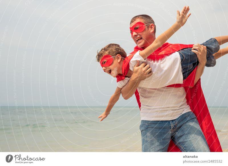 Vater und Sohn spielen tagsüber am Strand Superhelden. Die Leute haben Spaß im Freien. Konzept des Sommerurlaubs und der freundlichen Familie. Lifestyle Freude