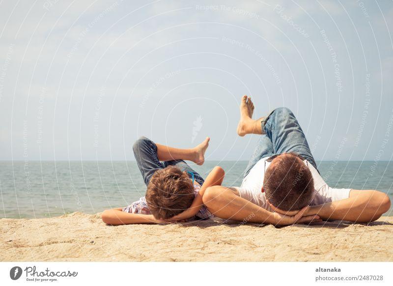 Vater und Sohn spielen zur Tageszeit am Strand. Die Menschen haben Spaß im Freien. Konzept des Sommerurlaubs und der freundlichen Familie. Lifestyle Freude
