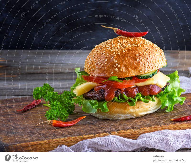 frischer hausgemachter Burger Fleisch Käse Gemüse Brot Brötchen Mittagessen Fastfood Tisch Restaurant Holz Essen groß lecker grün schwarz Hamburger Cheeseburger