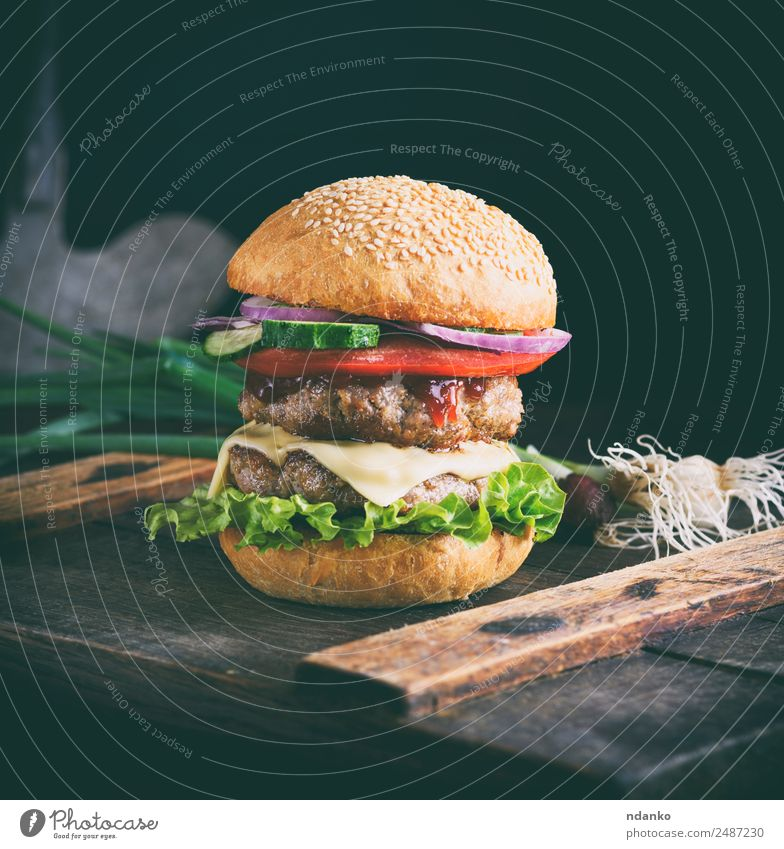 Sandwich mit zwei Fleischsorten Käse Gemüse Brot Brötchen Mittagessen Fastfood Tisch Holz Essen frisch groß lecker grün schwarz Burger Hamburger Lebensmittel