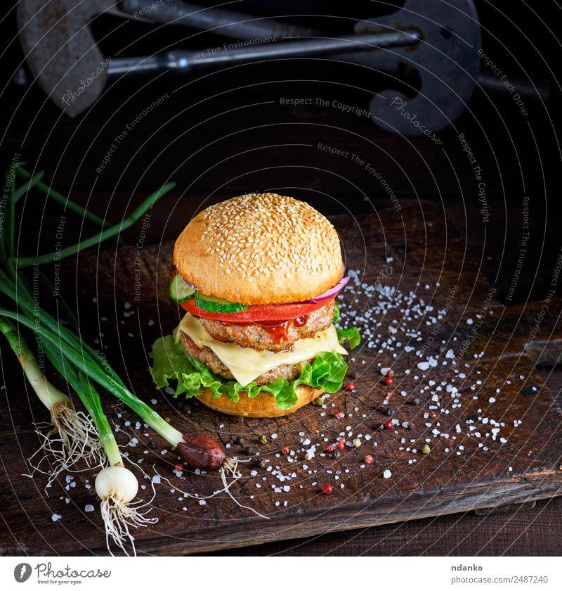 Sandwich mit zwei Fleischschnitzeln Käse Gemüse Brot Brötchen Mittagessen Fastfood Tisch Holz Essen frisch groß lecker grün schwarz Burger Hamburger