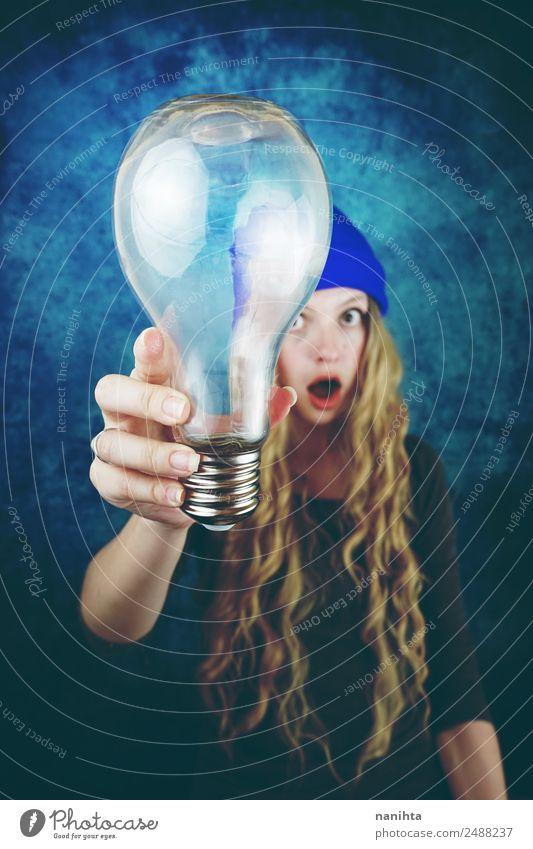 Junge Frau hält eine riesige Glühbirne in der Hand. Lifestyle Stil Design Haare & Frisuren Freizeit & Hobby Technik & Technologie Wissenschaften Fortschritt