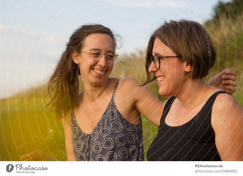 2 junge Frauen sitzen auf einer Wiese und lachen Lifestyle Freude Glück Freizeit & Hobby Mensch feminin Junge Frau Jugendliche Geschwister Schwester