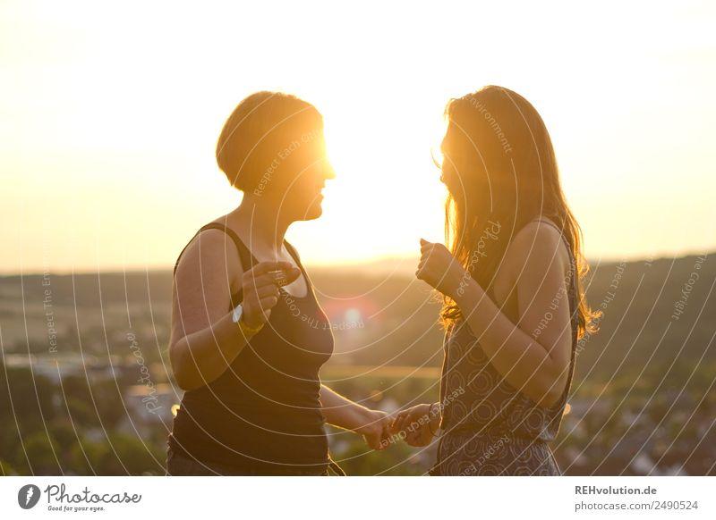 Zwei junge Frauen tanzen in der Sonne Oberkörper Schwache Tiefenschärfe Unschärfe Gegenlicht Sonnenuntergang Sonnenaufgang Sonnenlicht Licht Abend Außenaufnahme