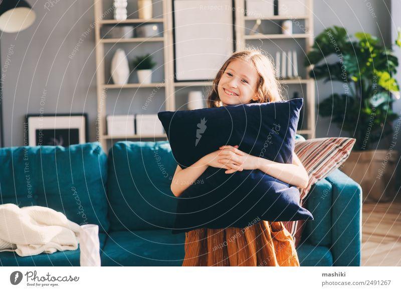 fröhliches fröhliches Kind Mädchen, das mit Kissen posiert. Lifestyle Glück Wohnung Haus Umzug (Wohnungswechsel) Dekoration & Verzierung Wohnzimmer Mensch