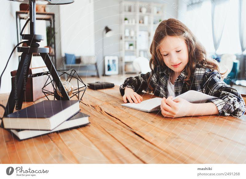 glückliches Schulmädchen, das Hausaufgaben macht. Kluges Kind, das hart arbeitet. Lifestyle lesen Tisch Erfolg Schule lernen Schulkind Kindheit Buch
