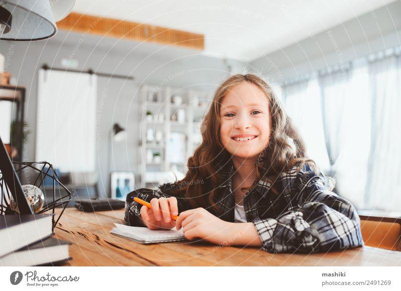 glückliches Schulmädchen, das Hausaufgaben macht. Kluges Kind, das hart arbeitet. Lifestyle lesen Erfolg Schule lernen Schulkind Kindheit Buch Lächeln schreiben